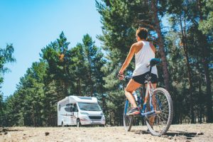 View of a young woman on a bicycle in front of an RV parked in the forest on a holiday adventure trip.