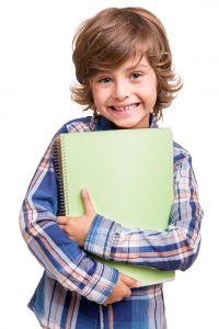 Little boy holding school books over white