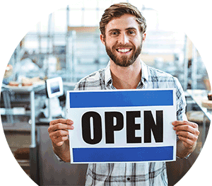 smiling business owner holding open sign
