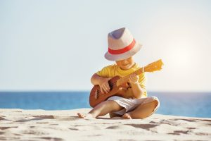 Little boy sitting on the beach playing guitar