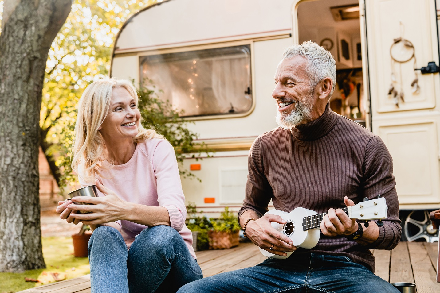 man playing the ukulele for his wife in front of their motor home